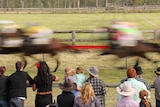 Crowd at a country race meet watch horses race past