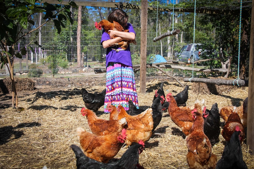 Jasmin hugs a chicken on a farm as other chickens at her feet look on.