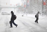 Pedestrians cross a snow-covered street in in Detroit during record breaking freezing weather.