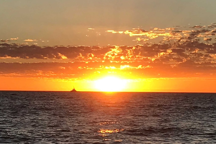 A bright orange sunset over the ocean.