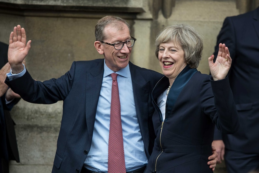 Theresa May and her husband Philip May wave to media and supporters.