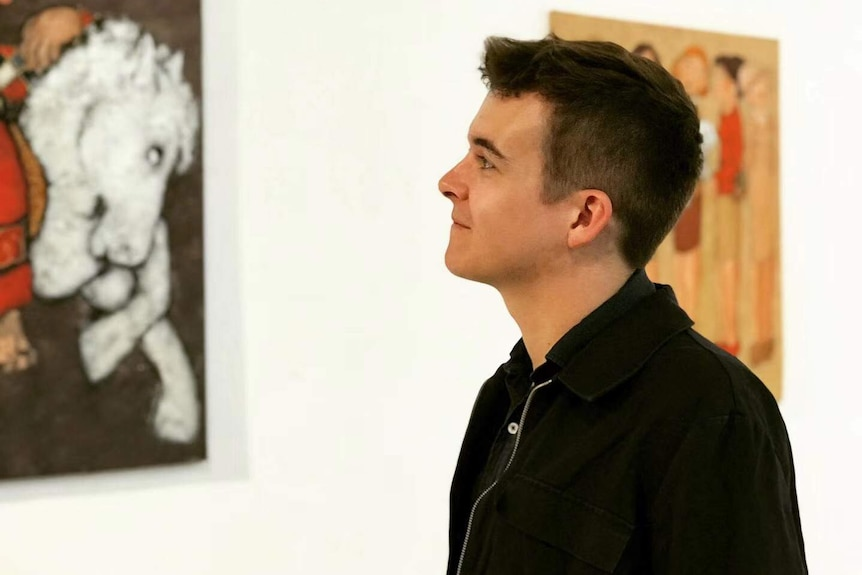 A man looking up and smiling in front of two framed art pieces