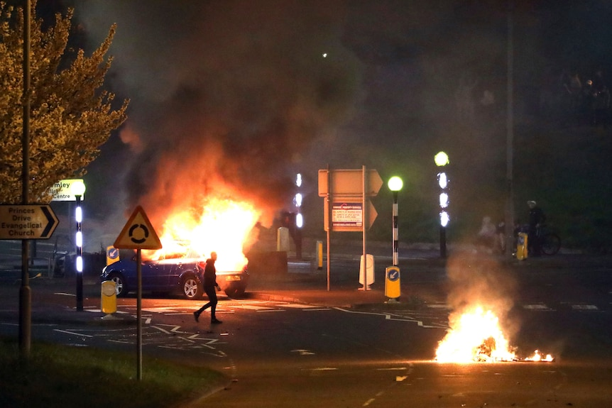 A man walks past a burning car as another fire burns in the street nearby.