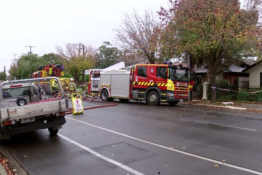 Fire fighting vehicles sit on a street at Ferryden Park in front of a home that was damaged in a fire