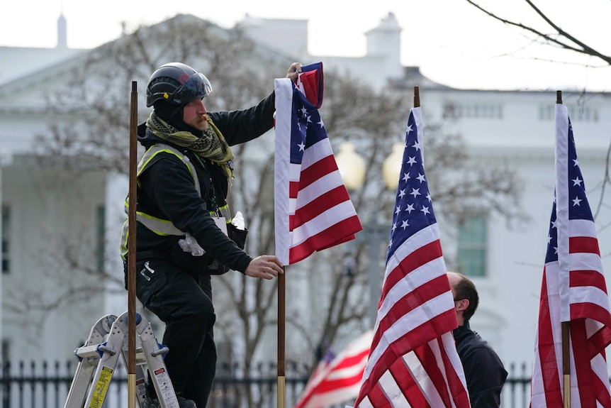 A man up a ladder adjusting American flags outside the White House