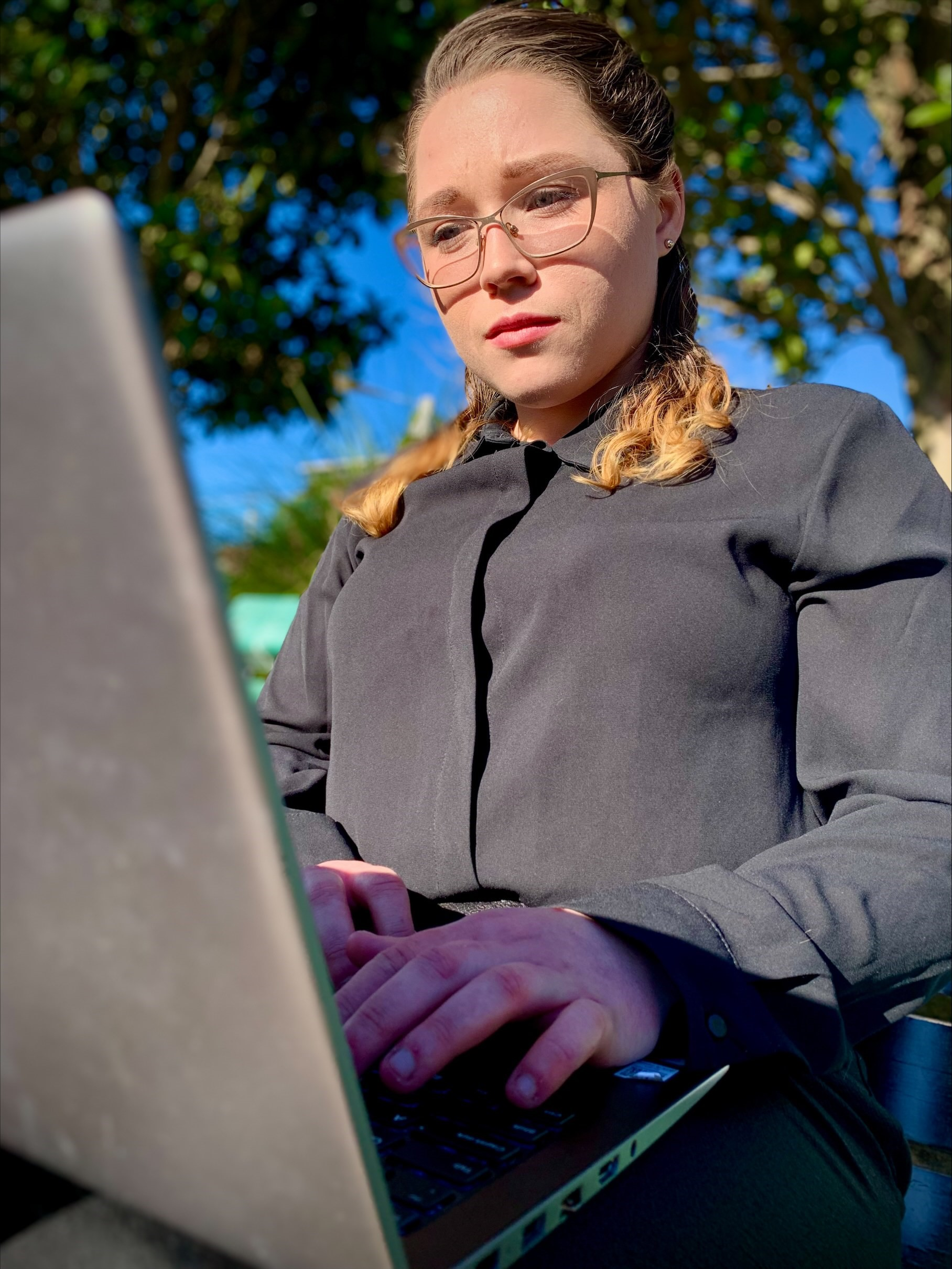 Melyssa Troy on her laptop at the park looking at a report her organisation did on consumer complaints.