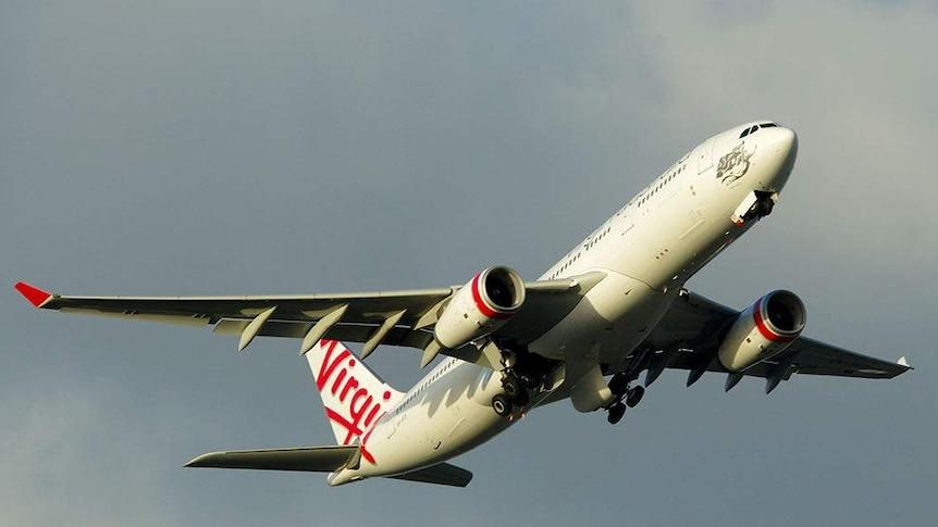 A Virgin plane flies in the sky. It is tilted upward after taking off.