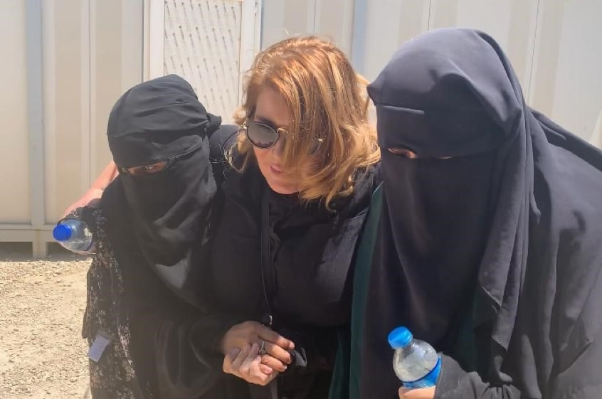 A woman walks with two women wearing hijabs