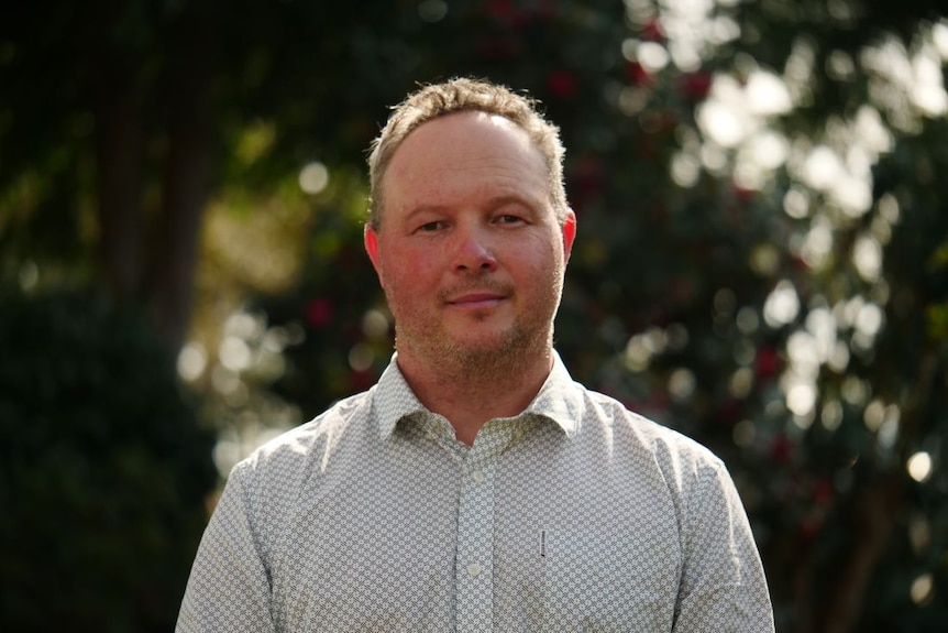 A man wearing a white and pale green shirt stands in a park.