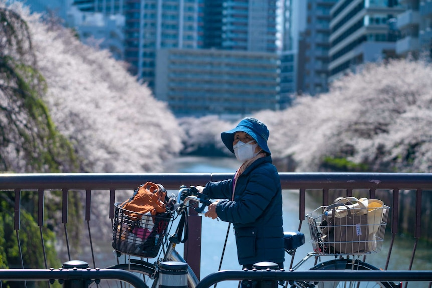 An older Japanese woman in a face mask wheeling her bike over a bridge