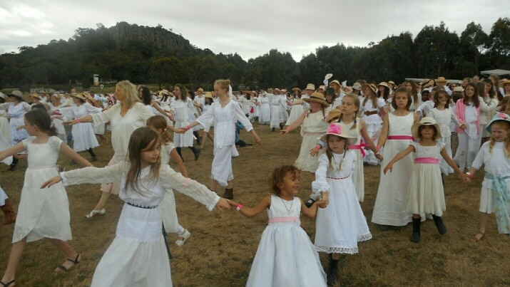 Dancers donned white lace dresses adorned with pink lace ribbons.