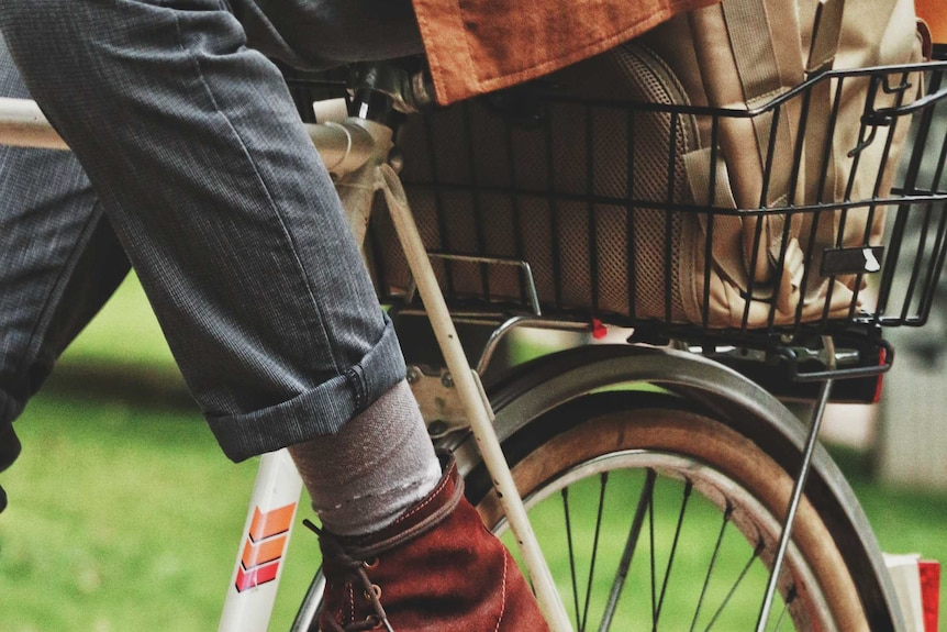Close up of man wearing dress shoes on a commuter bike