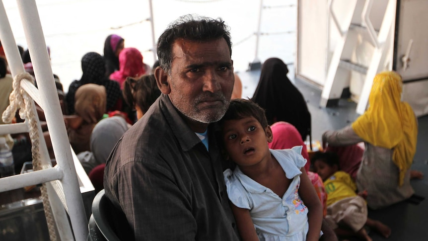A Rohingya refugee holds a young child.