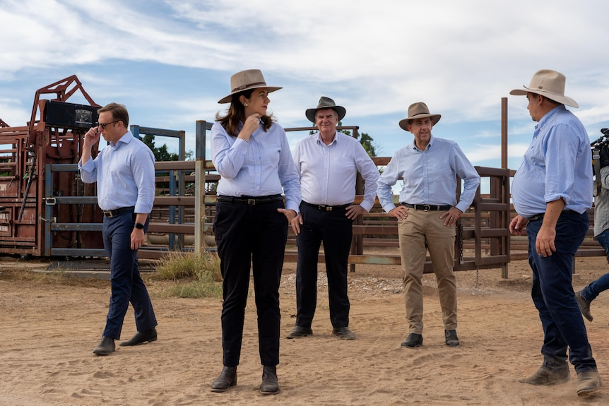 Four men and one woman dressed in blue shirts, trousers and hats stand on dusty ground in a cattle saleyard.