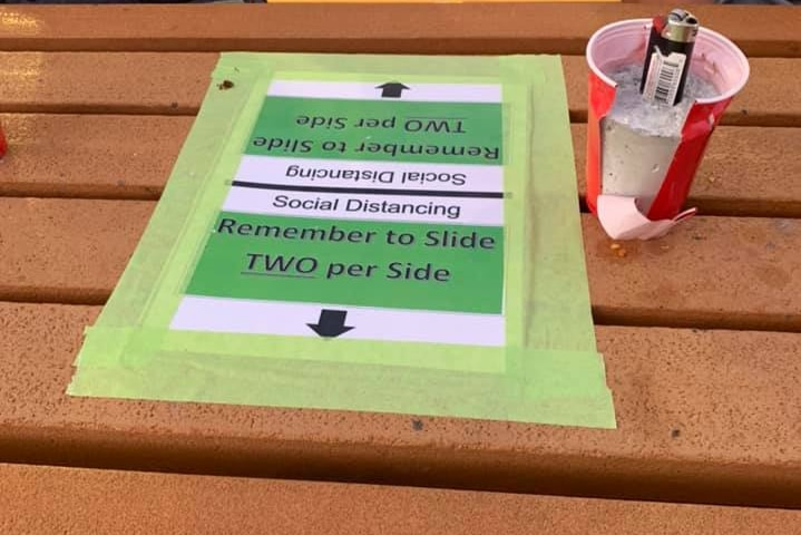 A tabletop displays signs that say only two people can sit on each side of the table.