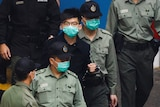 A man wearing glasses and a mask is escorted to a prison van by law enforcement officials.
