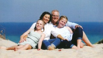 A family of two girls and parents sit on the beach smiling
