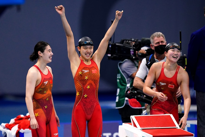 Three women wearing red tops and smiling