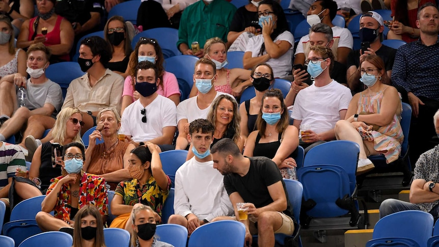 A group of tennis fans sit in the crowd at Melbourne Park for an Australian Open match.