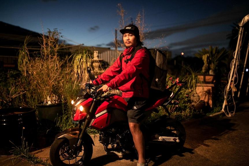 man on motor cycle in the backyard under dim lighting