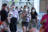 Masked passengers arrive at Adelaide Airport.