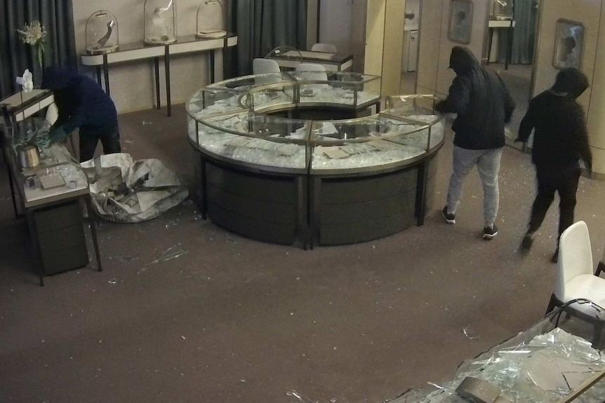 three hooded people in a jewellery store with its display cases smashed