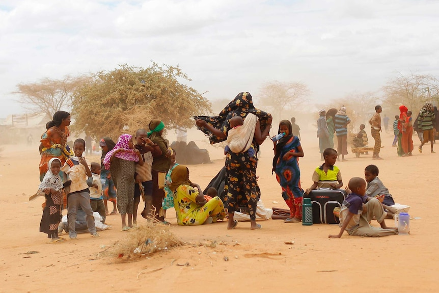 A group of refugees, including children, wait outside the world's largest refugee camp, as dust is blown into the air.
