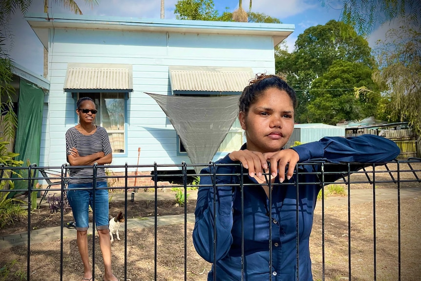 A young woman leans on a fence while another stands in the front yard of a house behind her.