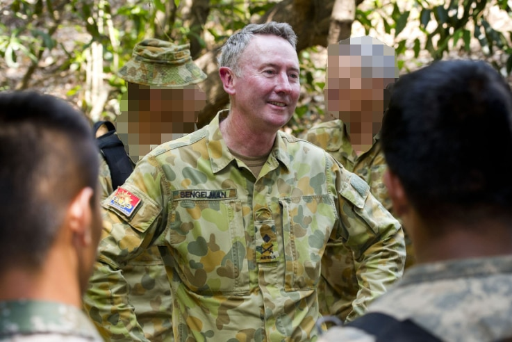 A man smiling, standing in military fatigues with other soldiers in front and behind of him in a forest location.