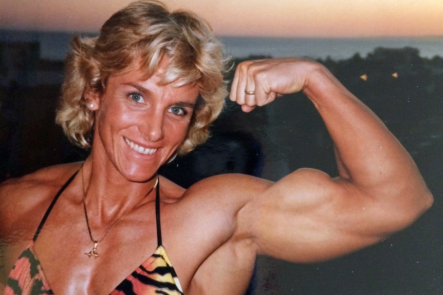 a female body builder pulls a muscle pose.