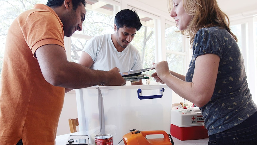 Three people loading items like torches, canned food and first aid kit into a plastic tub.