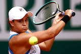 An Australian tennis players plays a backhand return at the French Open.