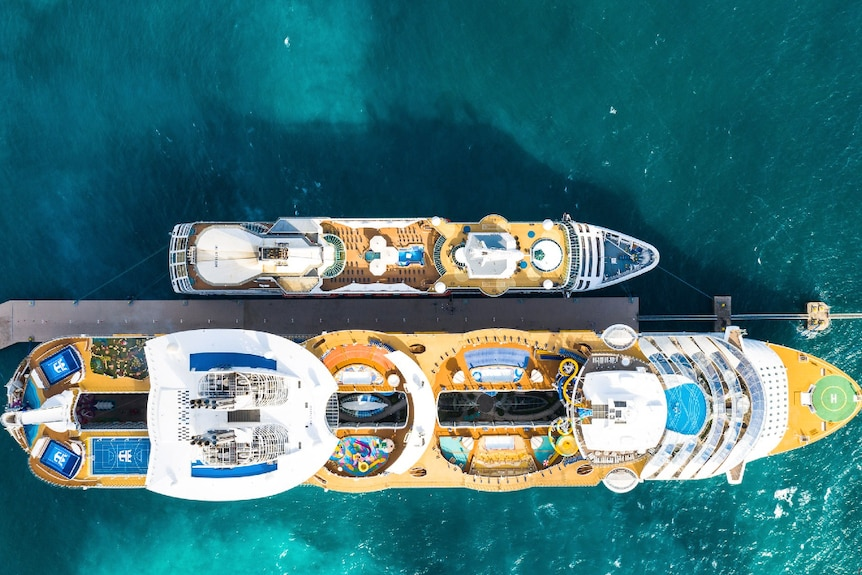 Aerial shot of a very large and much smaller cruise ship over green, blue ocean.