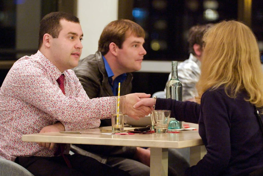 A young man shakes hands with a woman across a table as they meet at a dinner date