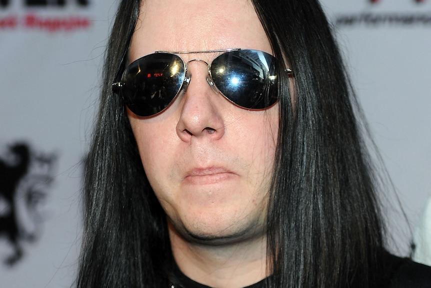 Joey Jordison with long black hair and waring dark sunglasses.