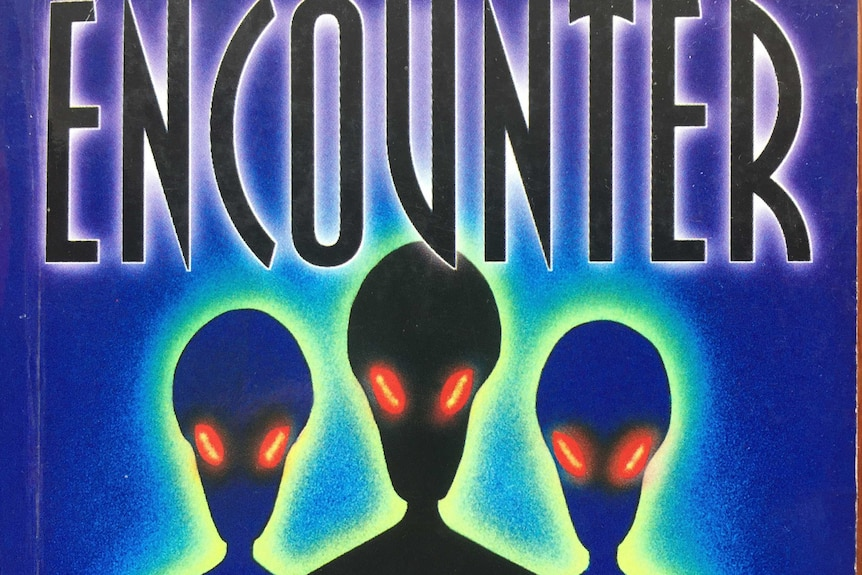 "Part of the front cover of a book, featuring aliens with glowing red eyes and the word ""Encounter""."