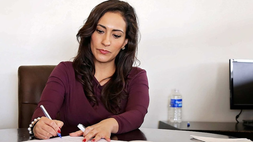 A woman in work attire writes on a document in an office.