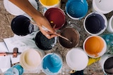 A person's hand dips a paint brush into a paint pot