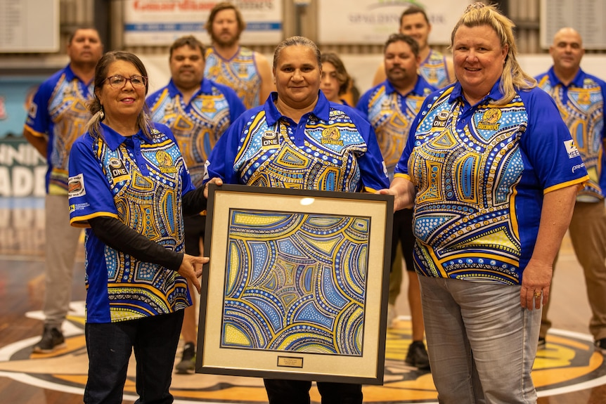 Three ladies with an Indigenous painting, with seven males in background, all wearing Indigenous uniform.