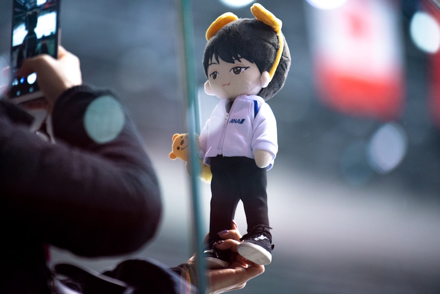 A plush toy of the figure skater Yuzuru Hanyu is held up and photographed.
