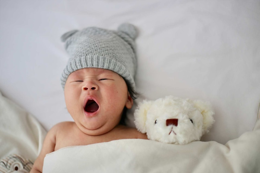 Cute yawning baby wearing a grey beanie in a bed for a story about why parents are choosing masculine names for their daughters.