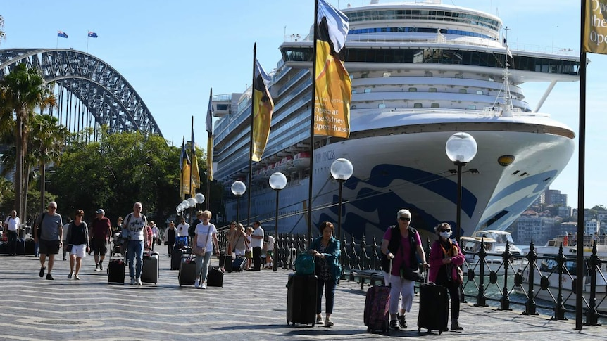 Several people walking past a large ship, as the Sydney Harbour Bridge can be seen in the background