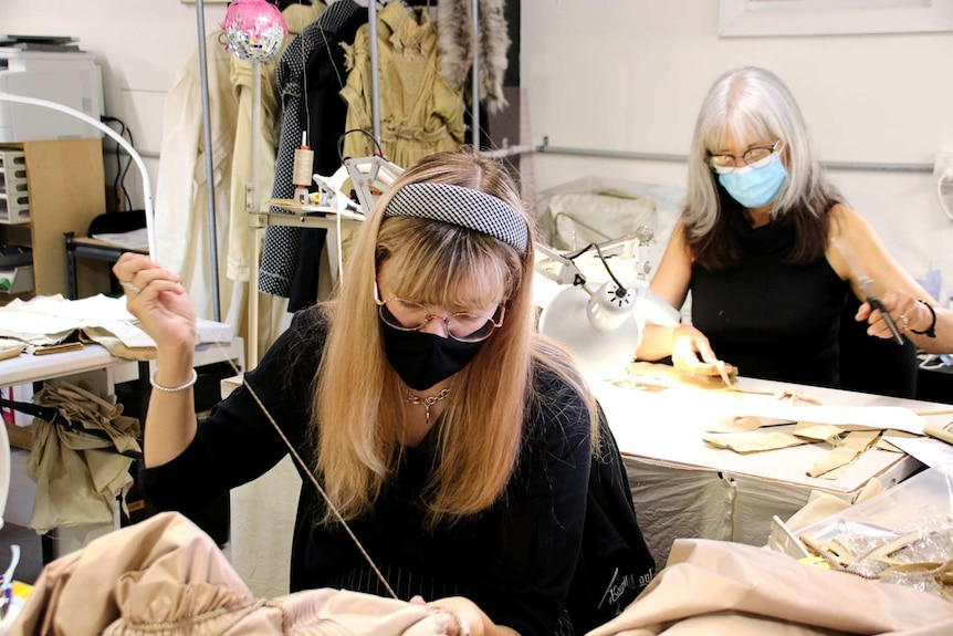 two women threading and cutting fabric in masks