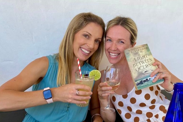 Two young women smiling, one holding a cocktail and the other holding a book