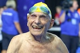 George Corones smiles to crowd in swimming cap and goggles.