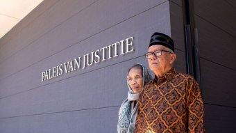An elderly Indonesian man and woman stand outside a courtroom.