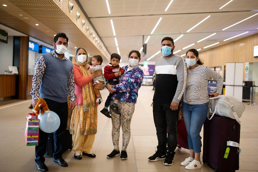 An extended family of two couples with a child each and a grandmother pose for a photo in an airport