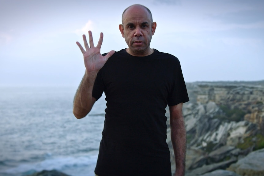 Steven Oliver standing on a cliff, ocean in the background, in a still from film Looky Looky Here Comes Cooky