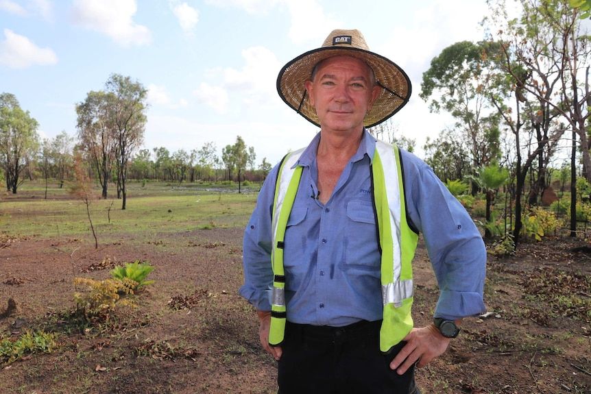 Danny Browne is in the middle of the bush wearing a wide hat, blue button-down shirt and bright yellow vest.
