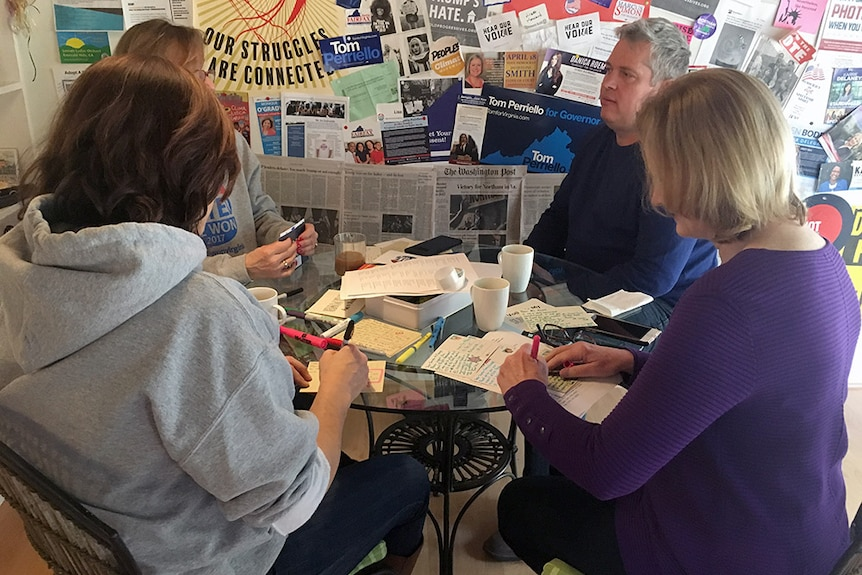 Four people sit around a table writing out postcards, with Democratic promotional material on the wall behind them.